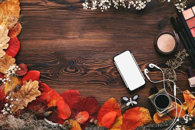 Conjunto de accesorios femeninos. hojas de otoño, teléfono inteligente y auriculares en madera