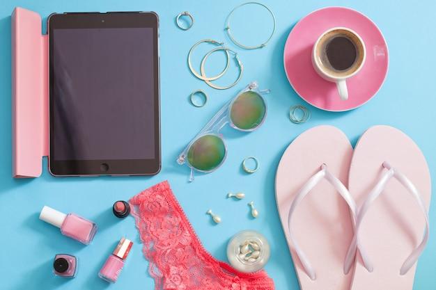 Conjunto de accesorios de mujer con estilo sobre fondo azul.