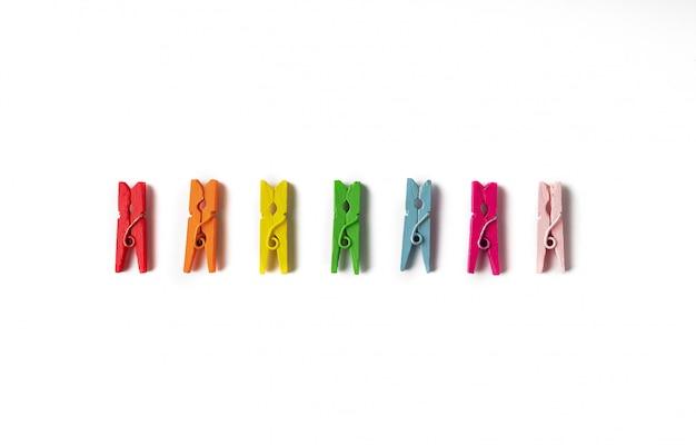 Conjunto de alfileres de madera multicolores sobre fondo blanco.
