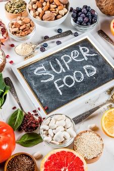 Conjunto de alimentos orgánicos de dieta saludable, superalimentos: frijoles, legumbres, nueces, semillas, verduras, frutas y verduras ... espacio de copia de fondo blanco
