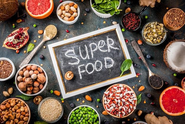 Conjunto de alimentos orgánicos de dieta saludable, superalimentos: frijoles, legumbres, nueces, semillas, verduras, frutas y verduras. fondo azul oscuro copia espacio vista superior