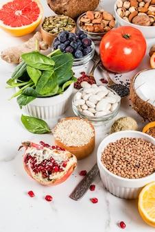 Conjunto de alimentos orgánicos de dieta saludable, superalimentos: frijoles, legumbres, nueces, semillas, verduras, frutas y verduras.