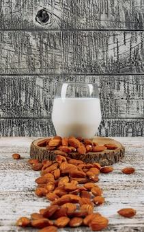 Conjunto de almendras y rebanada de madera y vaso de leche sobre un fondo gris de madera. vista lateral.