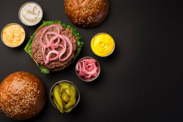 Conjunto de alto ángulo de sabrosas hamburguesas con salsas