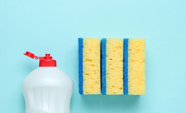 Conjunto de amas de casa para lavar platos. lavavajillas. botella de lavado de utensilios, esponjas sobre fondo azul pastel. vista superior.