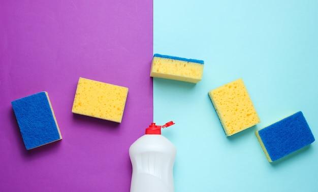 Conjunto de amas de casa para lavar platos. lavavajillas. botella de lavado de utensilios, esponjas sobre fondo azul violeta.