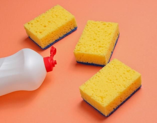 Conjunto de amas de casa para lavar platos. lavavajillas. botella de lavado de utensilios, esponjas sobre fondo de color coral.