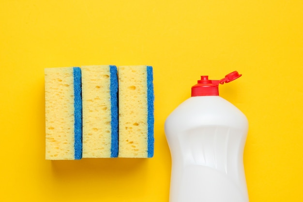 Conjunto de amas de casa para lavar platos. lavavajillas. botella de utensilios de lavado, esponjas sobre fondo amarillo. vista superior.