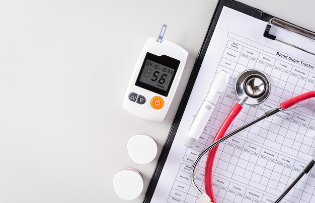 Conjunto de análisis de sangre y registro de seguimiento de azúcar con estetoscopio.