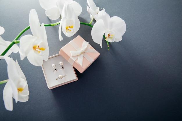 Conjunto de anillo y pendientes de plata con perlas en la caja de regalo con orquídea blanca.