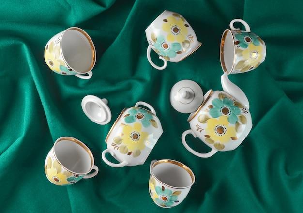 Conjunto antiguo de platos sobre un mantel de tela de color oscuro. tetera de cerámica, platillo, taza. vista superior.