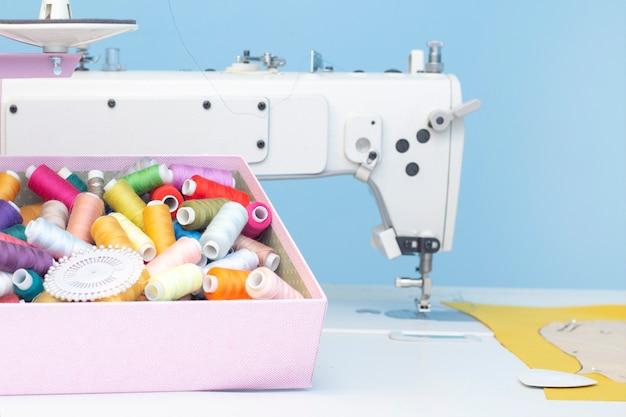 Un conjunto de artículos para costura: hilos, agujas, alfileres, tijeras, cinta métrica, etc.