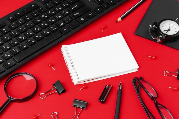 Conjunto de artículos de papelería en escritorio de oficina rojo