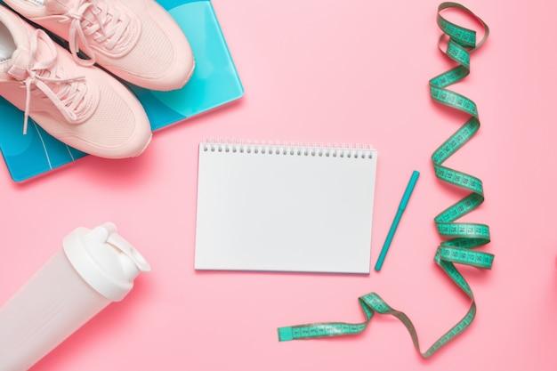 Conjunto de atleta. equipamiento deportivo: zapatillas, básculas, cinta métrica y agitador de proteínas de plástico sobre fondo rosa pastel.