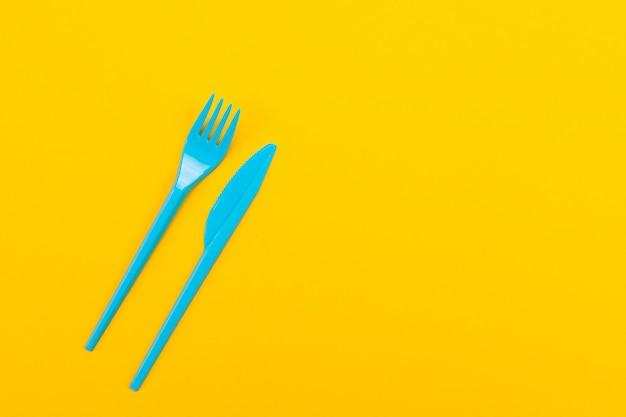 Conjunto azul de vibrantes tenedores y cuchillo aislado sobre fondo amarillo