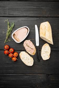 Conjunto de baguette sándwich de paté de hígado de pollo, sobre fondo de mesa de madera negra, vista superior plana, con espacio para copiar texto
