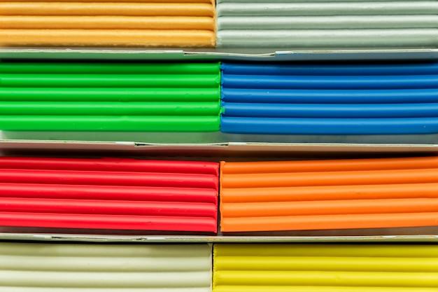Conjunto de barras de plastilina multicolores para modelar en mesa de madera. vista superior, educación y concepto de creatividad.