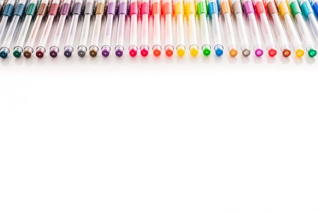 Conjunto de bolígrafos de colores dispuestos sobre una mesa de estudio blanca con espacio de copia aislado.