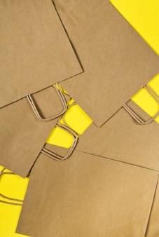 Conjunto de bolsas de papel artesanales para ir de compras en una mesa amarilla.