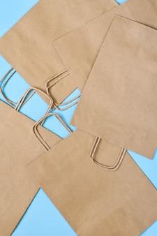 Conjunto de bolsas de papel artesanales para ir de compras en una mesa azul.