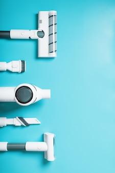 Un conjunto de boquillas y una aspiradora inalámbrica blanca en una fila sobre un fondo azul, espacio libre. vista superior