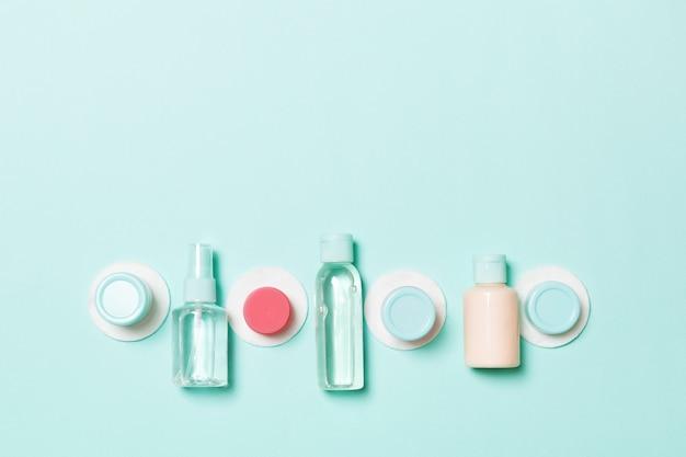Conjunto de botellas de cosméticos de tamaño de viaje sobre fondo azul. endecha plana de tarros de crema