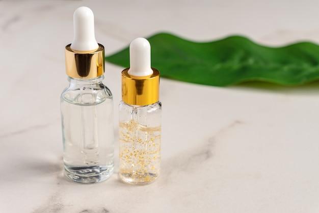 Conjunto de botellas de vidrio cosmético con un gotero en una canica