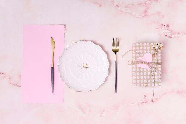 Conjunto de caja actual junto a plato, papel y cubiertos.