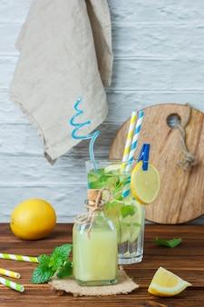 Conjunto de caja de madera y limones y tela blanca, tabla de cortar y vaso de jugo de limón sobre una superficie de madera y blanca. vista lateral.