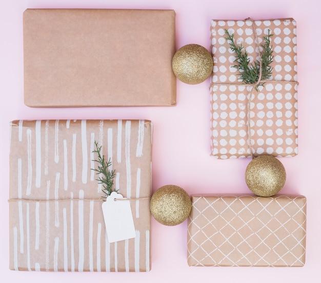 Conjunto de cajas presentes en envolturas cerca de bolas de navidad
