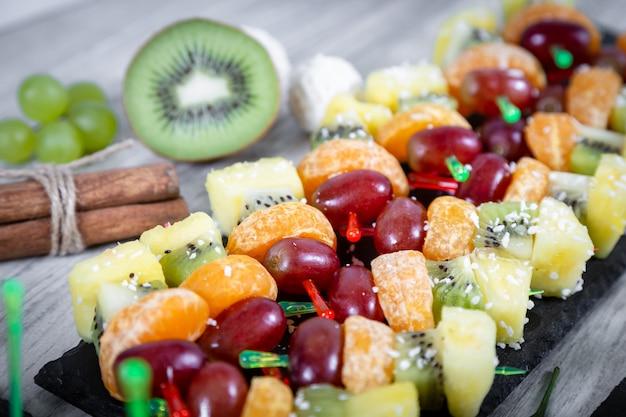 Conjunto de canapés de fruta en mesa de madera.