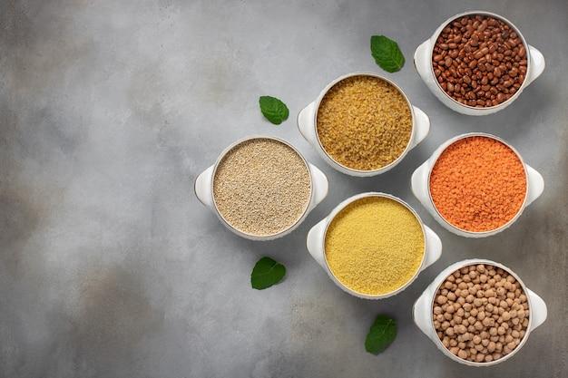 Conjunto de cereales: bulgur, cuscús, frijoles, quinua, lentejas, garbanzos copia espacio, vista superior