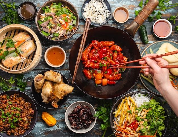 Conjunto de comida china variada en la mesa con mano femenina sosteniendo palillos desde arriba. mesa llena y festiva con todos los platos tradicionales chinos, cena o buffet estilo asiático, vista superior