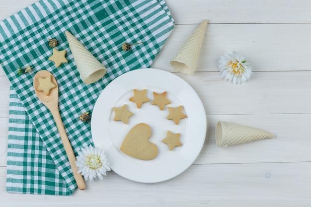 Conjunto de conos de galleta, flores y galletas en plato y cuchara de madera sobre fondo de toalla de cocina y madera. endecha plana.