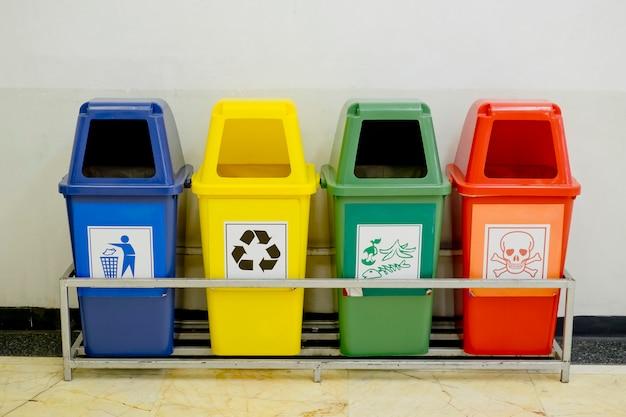 Conjunto de contenedores de diferentes colores con ruedas con el icono de residuos