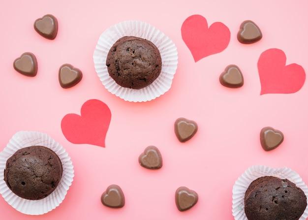 Conjunto de corazones de chocolate dulce cerca de muffins y tarjetas de san valentín