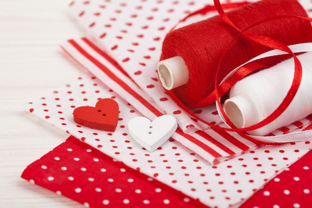 Conjunto para costura: tela, carretes de hilo, agujas, alfileres, botones, tijeras. artículos en colores rojo y blanco.