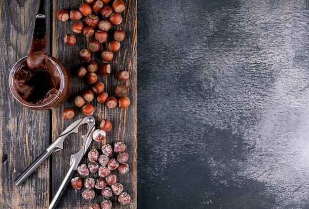 Conjunto de crema de cacao y cascanueces y avellanas sin cáscara sobre una mesa de madera oscura y piedra negra. vista superior.