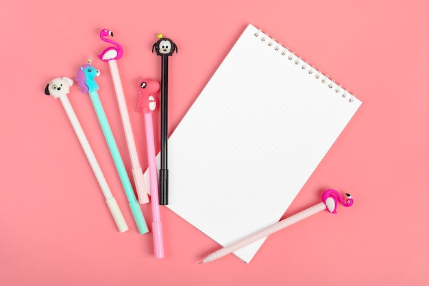 Conjunto de cuadernos para notas y bolígrafos sobre fondo rosa.