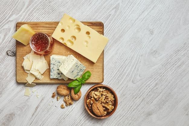 Conjunto de cuatro quesos en tabla de cortar rústica aislado en el lateral de la mesa de madera blanca cepillada se sirve para el desayuno con miel rústica y nueces en un tazón marrón con hojas de albahaca. vista superior