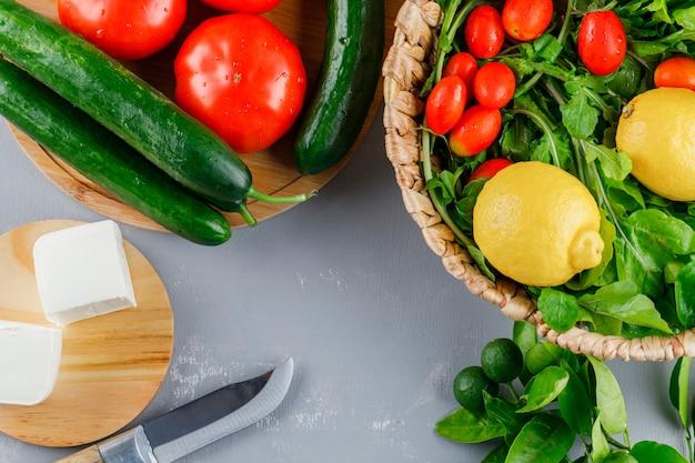 Conjunto de cuchillo, limón, pepino, queso, verduras y tomates en una tabla de cortar sobre una superficie gris