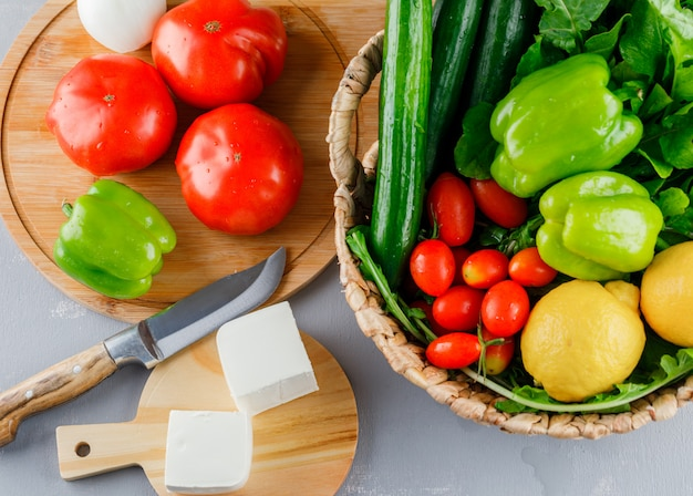 Conjunto de cuchillo, pimiento verde, limón, pepino, queso, verduras y tomates en una tabla de cortar sobre una superficie gris
