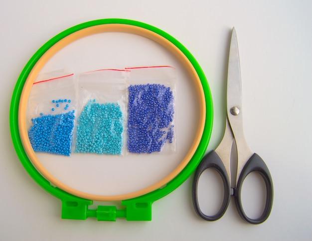 Conjunto de cuentas azules y azules en aro y tijeras sobre lienzo blanco para bordados, pasatiempos y costura.