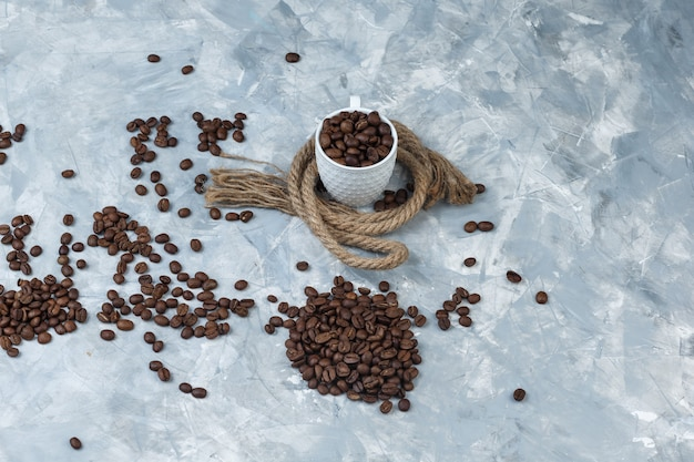 Conjunto de cuerdas y granos de café en una taza sobre un fondo de mármol azul. vista de ángulo alto.