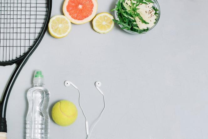 Conjunto de comida sana y equipo de tenis