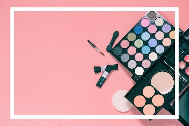 Conjunto de cosméticos decorativos sobre fondo rosa claro colorido.