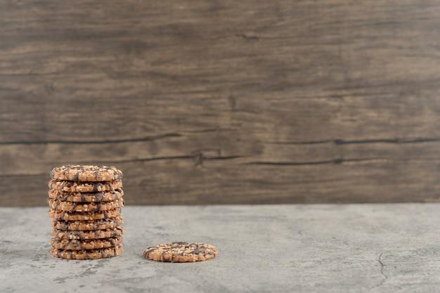Conjunto de deliciosas galletas dulces con jarabe de chocolate aislado sobre un fondo de piedra.