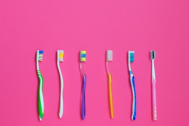 Conjunto de diferentes cepillos de dientes sobre fondo rosa.