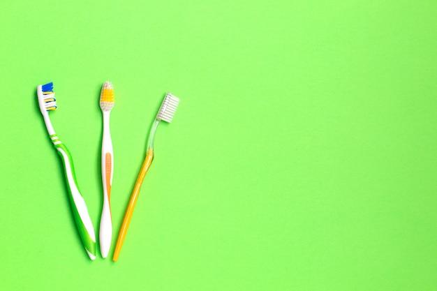 Conjunto de diferentes cepillos de dientes sobre fondo verde.