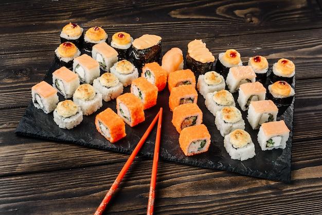 Conjunto de diferentes rollos y sushi en un plato con palillos.